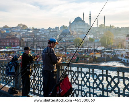ISTANBUL - APRIL 27: The Turks are fishing on Galata Bridge April 27, 2015 in Istanbul, Turkey. The Blue Mosque and fountains.