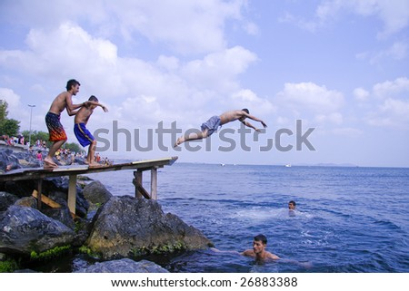 ISTANBUL - AUGUST 5: Teenagers jump into Bosphorus sea from wooden pier in Istanbul, Turkey on August 5, 2007. The Bosphorus is the strait that separates the continents of Europe and Asia. - stock photo