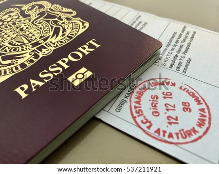 ISTANBUL - DECEMBER 12: UK Passport and Turkish entry immigration paper document with Istanbul Ataturk International Airport Stamp in red ink on December 12, 2016 in Istanbul, Turkey.