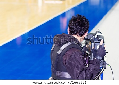 ISTANBUL - JANUARY 20: Professional cameraman records live while THY Euroleage Top 16 Basketball Championship, Efes Pilsen vs Montepaschi Siena January 20, 2011 in Istanbul - stock photo