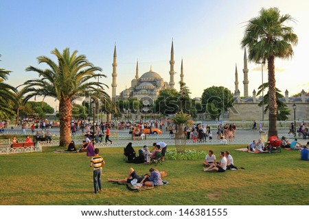 ISTANBUL - JUL 15: Muslims and Tourists enjoy the sun on Sultanahmet Square on Ramadan, July 15, 2013 in Istanbul, Turkey. At the end of day the fast is broken with prayer and a meal called the iftar. - stock photo