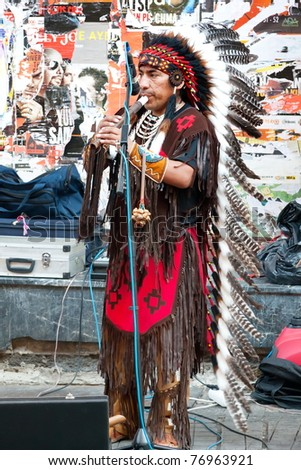 ISTANBUL - JULY 06: An unidentified Amerindian performs in traditional costume during street show at Istiklal Street on July 06, 2010 in Istanbul.Beyoglu district is the major strolling street in city - stock photo