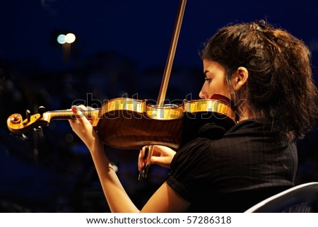 ISTANBUL - JULY 11: Members of the Maltepe Symphonic Orchestra perform live at Maltepe open air stage on July 11, 2010 in Istanbul. Musician playing violin. - stock photo