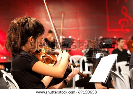 ISTANBUL - JULY 11: Members of the Maltepe Symphonic Orchestra perform live at Maltepe open air stage on July 11, 2010 in Istanbul, Musician playing violin - stock photo