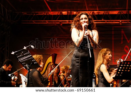 ISTANBUL - JULY 11: Members of the Maltepe Symphonic Orchestra perform live at Maltepe open air stage on July 11, 2010 in Istanbul. Soprano Selva Erdener - stock photo