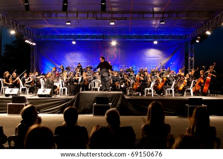 ISTANBUL - JULY 11: Members of the Maltepe Symphonic Orchestra perform live at Maltepe open air stage on July 11, 2010 in Istanbul - stock photo