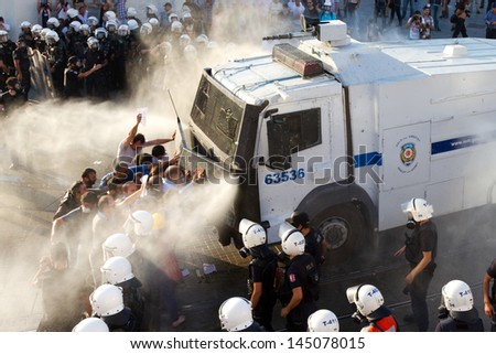 ISTANBUL - JULY 06: Riot Control Vehicle interfere Taksim Solidarity and Gursel Tekin with water spray and tear gas during protests on July 06, 2013 in Istanbul, Turkey.