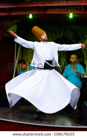 ISTANBUL - JULY 25: Sufi whirling dervish (Semazen) dances at Sultanahmet during month of Ramadan on July 25, 2012 in Istanbul. Semazen conveys God's spiritual gift to those are witnessing the ritual. - stock photo