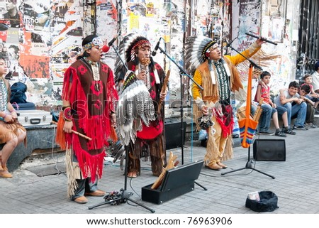ISTANBUL - JULY 06: Unidentified Amerindians perform in traditional costumes during street show at Istiklal Street on July 06, 2010 in Istanbul. Beyoglu district is the major strolling street in city. - stock photo