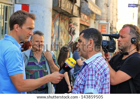 ISTANBUL - JUNE 17, 2013: Labor unions call 1 day nationwide strike over crackdown at Gezi Park in Turkey. RTL TV journalist reports live the protest at Istiklal Street. Young Reporter Breaking News - stock photo