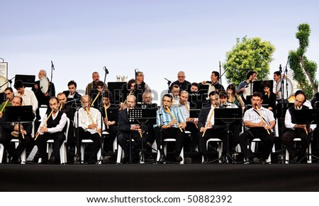 "ISTANBUL - SEPTEMBER 18: Members of the ""Kirk Ney Bir Nefes"" reed flute orchestra perform on stage for the month of Ramadan at Sultanahmet Square. September 18, 2009 in Istanbul, Turkey. Flute Players - stock photo"
