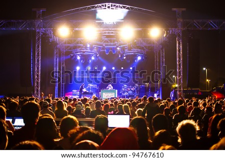 ISTANBUL - SEPTEMBER 18: Pop star Ajda Pekkan performs live during a concert at Maltepe on September 18, 2011 in Istanbul, Turkey. Concert stage and excited spectators are pictured. - stock photo