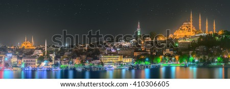 Istanbul skyline from Galata bridge by night, with Suleymaniye mosque and fish boat ferry - stock photo