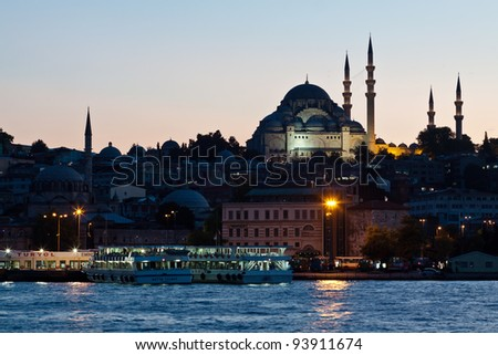 Istanbul skyline from Galata bridge by night, with Suleymaniye mosque and fish boat restaurants in Eminonu - stock photo