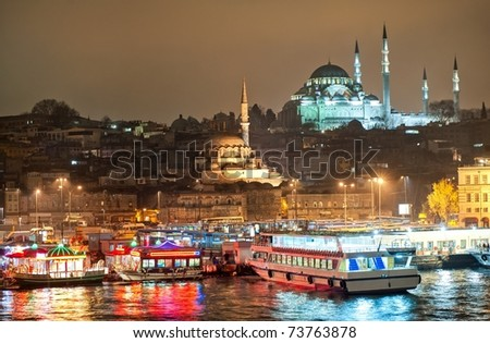 Istanbul skyline from Galata bridge over Golden Horn by night, with Suleymaniye mosque and fish boat restaurants in Eminonu - stock photo
