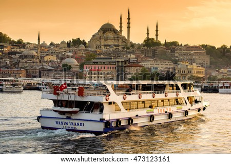 ISTANBUL, TURKEY - APRIL 18, 2016: Passanger ferry going to Eminonu Ferry station with Rustem Pasha mosque (Rustempasa Camii) on background at sunset, Istanbul, Turkey on 18 of April 2016.