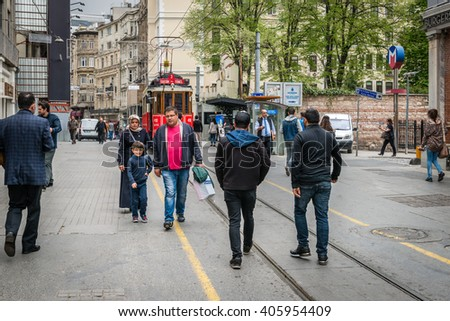 Istanbul, Turkey - April 08, 2016: People are walking down the Istiklal street on the background of red tram in Istanbul, Turkey