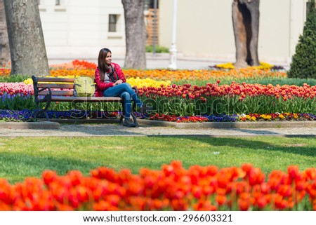 ISTANBUL,TURKEY - APRIL 08, 2015: Tourist in a garden near Sultanahmet square,The Sultanahmet square is the popular tourist place with the numerous landmarks and museums, on April 08 Istanbul, Turkey - stock photo