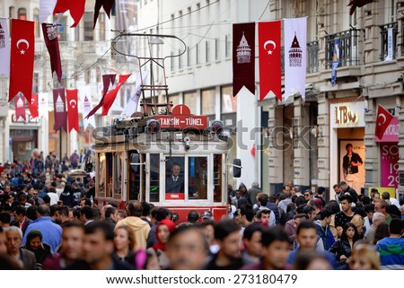 ISTANBUL, TURKEY - APRIL 28, 2015 :  View of the famous and historic Red Tram on Istiklal street in Istanbul through a crowd of pedestrians. The Red Tram running between Taksim and Tunel square. - stock photo