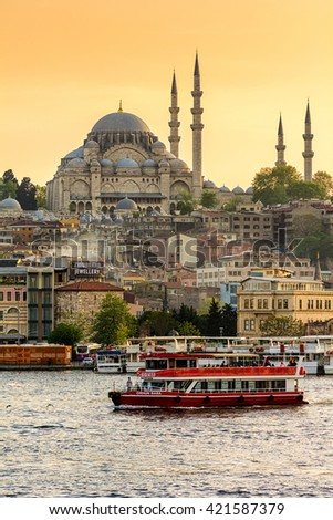 ISTANBUL, TURKEY - APRIL 18, 2016: View of the Rustem Pasha mosque (Rustempasa Camii)  from the Galata Bridge at sunset with tourist ship on the Golden Horn, Istanbul, Turkey.