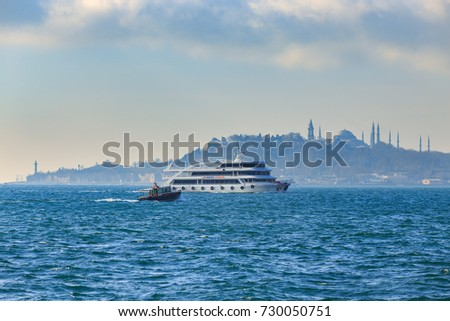 ISTANBUL, TURKEY - FEB 1, 2013: Tourists boat cruise in the Bosphorus strait with Islamic mosque as background in Istanbul, Turkey.