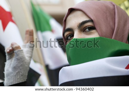ISTANBUL,TURKEY-FEBRUARY 5: An unidentified woman participates with a group of people who staged a demonstration in front of the Syrian Consulate, protesting Syrian authorities' violent crackdown in Homs, on Feb 5, 2012 in Istanbul, Turkey - stock photo