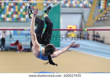 ISTANBUL, TURKEY - FEBRUARY 15, 2015: Athlete Esengul Gokdemir high jump during Turkcell Juniors and Seniors Athletics Turkey Indoor Championship in Asli Cakir Alptekin Athletics hall - stock photo