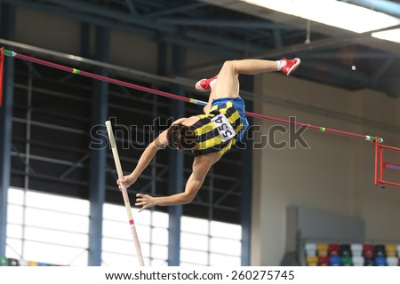ISTANBUL, TURKEY - FEBRUARY 15, 2015: Athlete Mustafa Tilki pole vaulting during Turkcell Juniors and Seniors Athletics Turkey Indoor Championship in Asli Cakir Alptekin Athletics hall - stock photo