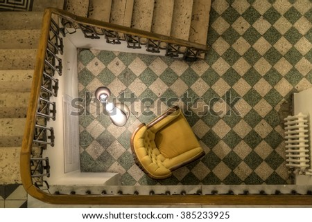 Istanbul,Turkey, February 04, 2016: Top view to Spiral Stair and empty armchair with gloomy light from vintage Istanbul flat - stock photo