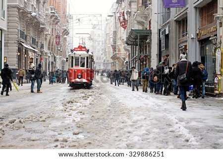 ISTANBUL,TURKEY-FEBRUARY 18: Unidentified pedestrians walk down Istiklal Street on a snowy day on February 18, 2015 in Istanbul, Turkey.Istiklal Street is one of the popular destinations in Istanbul. - stock photo