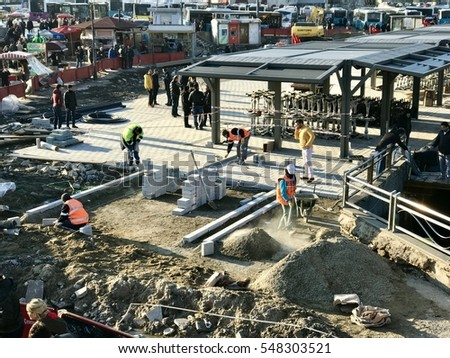 ISTANBUL, TURKEY - JANUARY 02, 2017:Eminonu district in istanbul.Construction workers renovate a walkway with paving stones in the city centre of Eminonu. Passers-by must take a detour