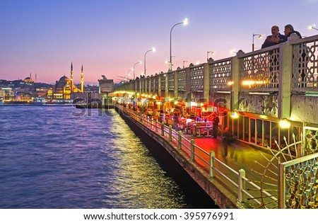 ISTANBUL, TURKEY - JANUARY 21, 2015: The bright lights on the ground level of Galata bridge attracts people to the fine fish restaurants and cozy cafes, located there, on January 21 in Istanbul.