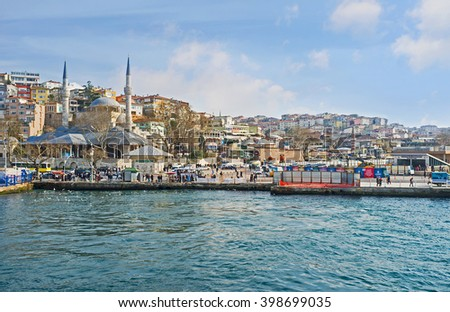 ISTANBUL, TURKEY - JANUARY 21, 2015: The Uskudar quay with one of its best-known landmarks - Mihrimah Sultan Mosque, on January 21 in Istanbul.