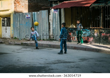 Istanbul, Turkey - January 12, 2016: Three boys are playing ball in the street of Istanbul, Turkey - stock photo