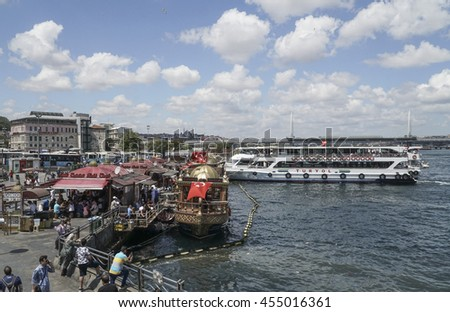 ISTANBUL, TURKEY - JULY 19, 2016: Eminonu district with many facilities to eat such as floating restaurants and carts with fresh bakery, hot corn or roasted chestnuts in Istanbul, Turkey. - stock photo