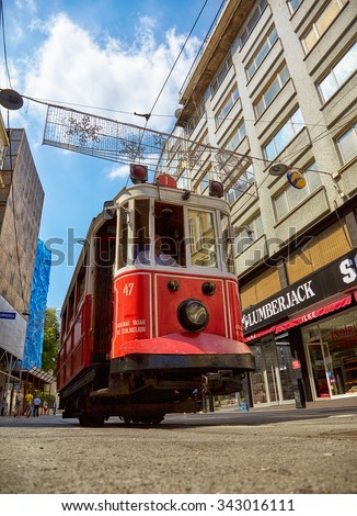 ISTANBUL, TURKEY - JULY 13, 2014:  Heritage trams of a Taksim-Tunel Nostalgia Tramway line operates on Istiklal Street between Taksim Square and underground railway line - Tunnel.  Istanbul, Turkey