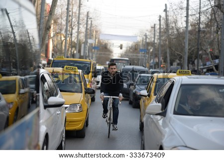ISTANBUL, TURKEY, 7 JUNE 2015, A man try cycling between cars on Istanbul traffic. - stock photo