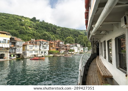 ISTANBUL, TURKEY, JUNE 8, 2013 :Passenger ferry and houses at the coastline of Anadolu Kavagi, a famous fishing town at the edge of Bosphorus with many restaurants and touristic facilities.  - stock photo