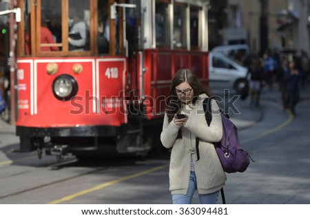 ISTANBUL, TURKEY, 4 NOVEMBER 2015, People look at mobile phone while walking on the street. - stock photo