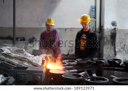 ISTANBUL, TURKEY - NOVEMBER 10: Turkish workers are hard working in a foundry on November 10, 2013 in Istanbul, Turkey. Molten metal poured from ladle. - stock photo