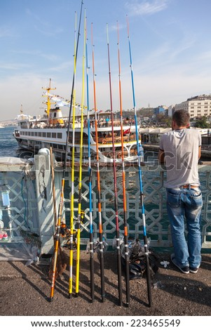 ISTANBUL, TURKEY - OCT 7, 2014: Local citizens fishing on the Galata Bridge in Istanbul, Turkey.