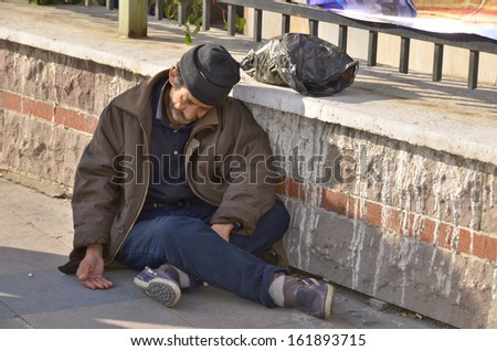 ISTANBUL TURKEY OCTOBER 08: Homelessness Muslim man sleep on the side walk  in the heart of downtown Istanbul on october 08 2013. The absolute poverty line for Turkey was US $4 per capita per day. - stock photo