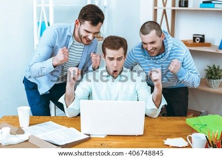 IT company. Young programmers working with laptop. Nice office interier. Professional coders looking at laptop and rejoicing - stock photo
