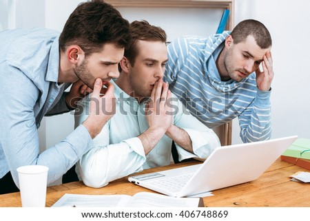 IT company. Young programmers working with laptop. Nice office interier. Professional coders looking at laptop - stock photo