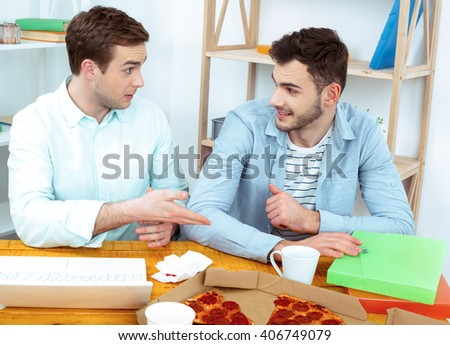 IT company. Young programmers working with laptop with pizza. Nice office interier. Professional coders looking at laptop - stock photo