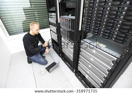 IT consultant calling for help in datacenter - stock photo