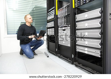 It consultant monitors servers in datacenter - stock photo