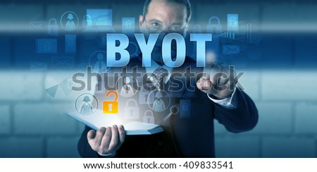 IT director is touching BYOT on an interactive visual screen. Business work trend metaphor and information technology concept for the practice to Bring Your Own Technology to the workplace.