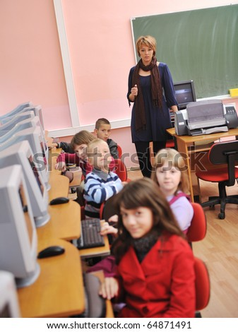 it education with children group  in school at computer science class learning leassons and practice typing