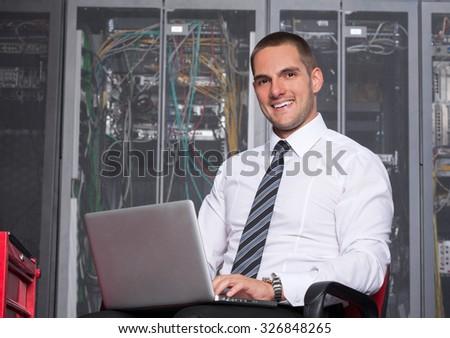 it engeneer businessman with thin modern aluminium laptop in network server room - stock photo